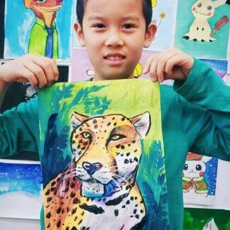 image of student holding artwork of leopard
