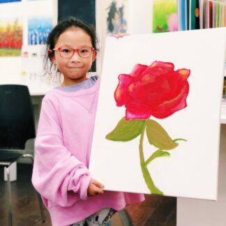image of student holding painting of rose