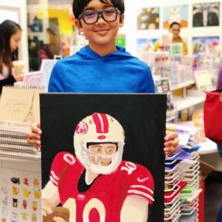 student holding art football player