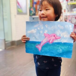 student showing art pink dolphin