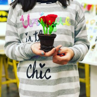 student holding flower plant clay