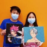 2 students holding anime drawings