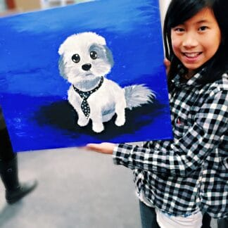 a girl showing her painting of a puppy