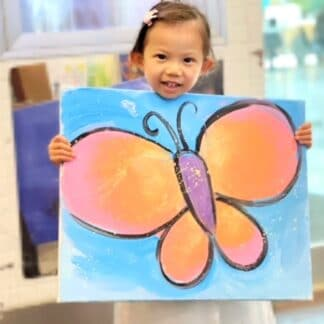 image of a student holding an orange and pink butterfly painting