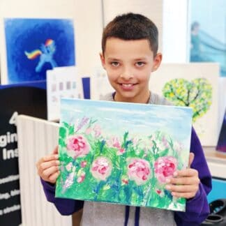boy holding canvas painting of pink flowers with green and blue background